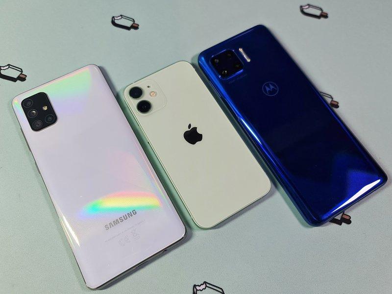 iPhone 12 mini galaxy a71 ja motorolan puhelimen vierellä