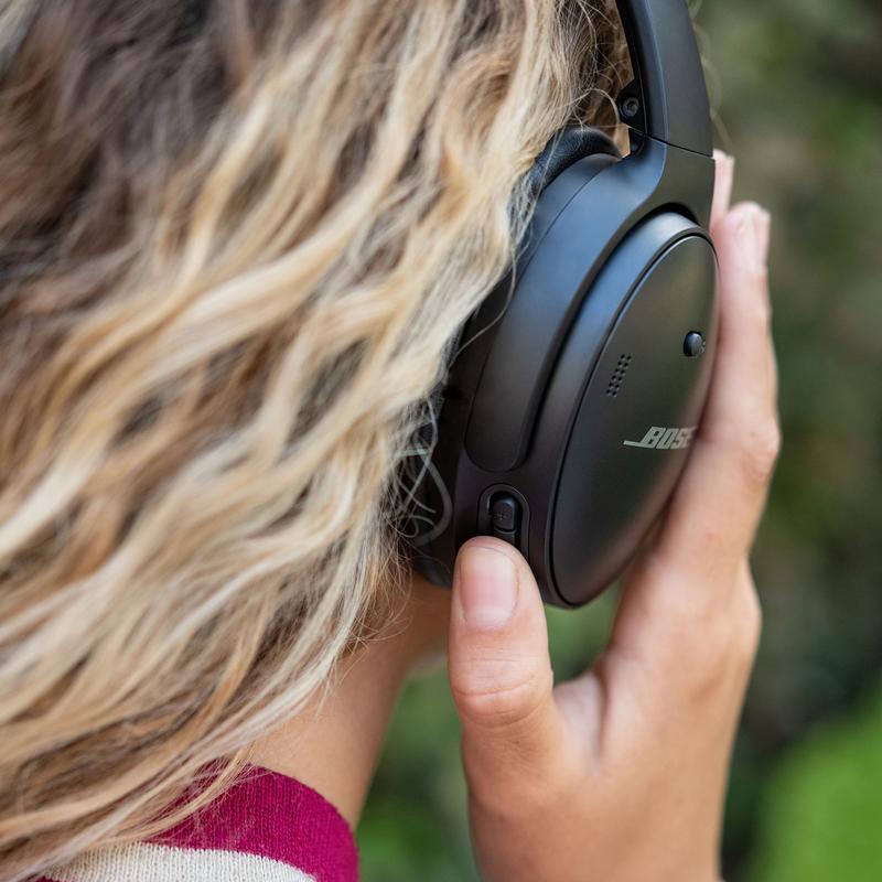 mustat QC45 kuulokkeet henkilön päässä