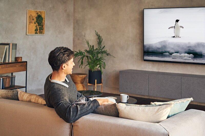 SRS-NB10 -kaiuttimet televisiota katsovan miehen kaulassa